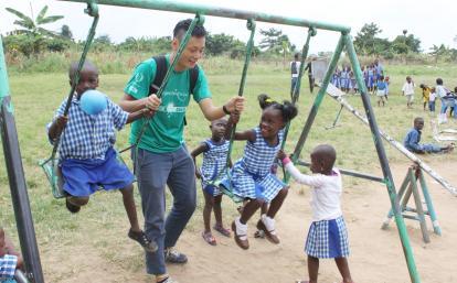 ブランコで遊ぶガーナの子供たちを見守る日本人チャイルドケアボランティア